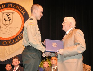 """Richard Morey (right), coordinator of South Florida State College's Criminal Justice programs, presents the """"top firearms score"""" to Brad Webster, third squad leader, for completing 194 out of 203 during the Basic Law Enforcement commencement service on Thursday, Feb. 5, in the SFSC Theatre for the Performing Arts."""