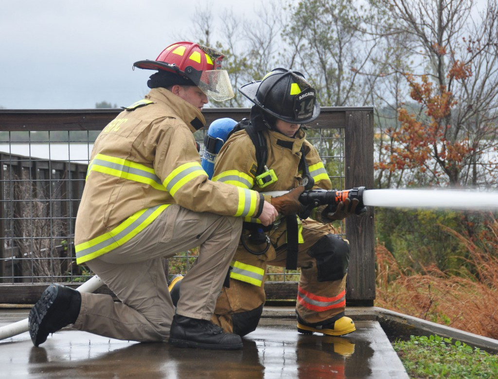 SFSC instructor Eric Hanks works with a recruit on the proper technique for deploying a hose.