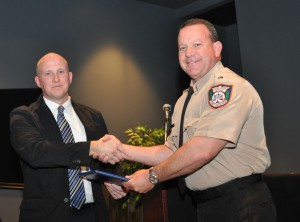 Cadet James S. Sottile accepting his diploma from Michael Huften, SFSC's coordinator of criminal justice training.