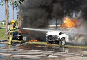 A firefighter extinguishes an automobile fire in a class offered by the Great Florida Fire School.