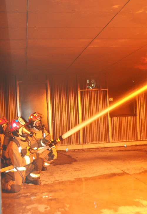 Three firefighters use a hose to douse fire in the ceiling of the college's new burn room during the Great Florida Fire School.