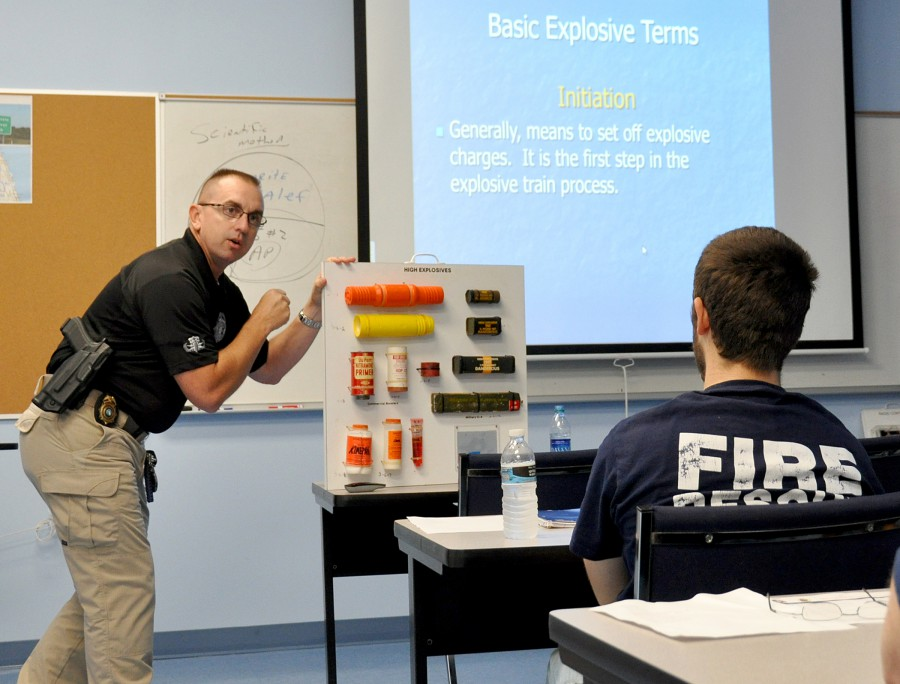 Instructor Brandon Ball explains basic explosive terms with a Powerpoint presentation and shows simulated explosive devices firefighters could encounter in the course of their work.