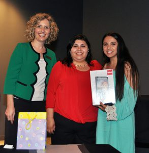 Jamie Bateman, mentor Danielle Ochoa, and Take Stock graduate Rosie Fimbres, who show the laptop computer she won.