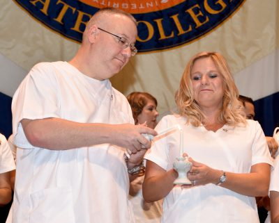 Former Class President Patrick Carey III lights the lamp held by Susan Decker during the Associate Degree in Nursing (ADN) pinning ceremony.