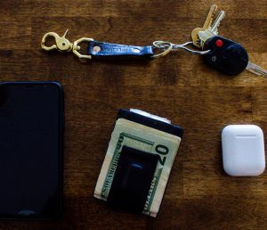 Photo of wallet, keys, phone, ear buds