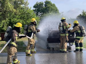 Fire Science students spraying water on a metal car form