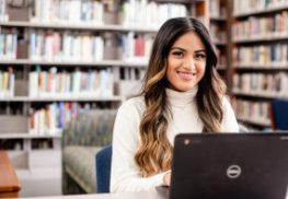 Female student with laptop in library