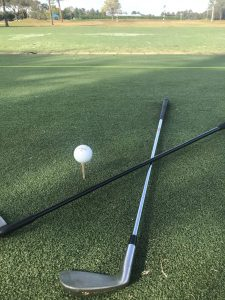 Golf ball on a tee and a golf club laying on the ground next to it