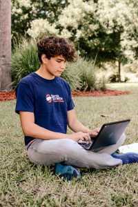 Male student with curly hair sitting on the lawn and typing on a laptop.