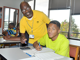 Male teacher assists a young man with course work in an Adult Education classroom.