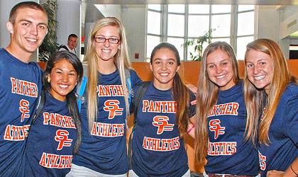 A diverse group of students poses while wearing Panther Athletics t-shirts