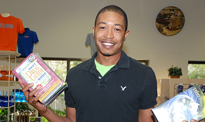 A smiling African-American man holds up textbooks in the campus bookstore