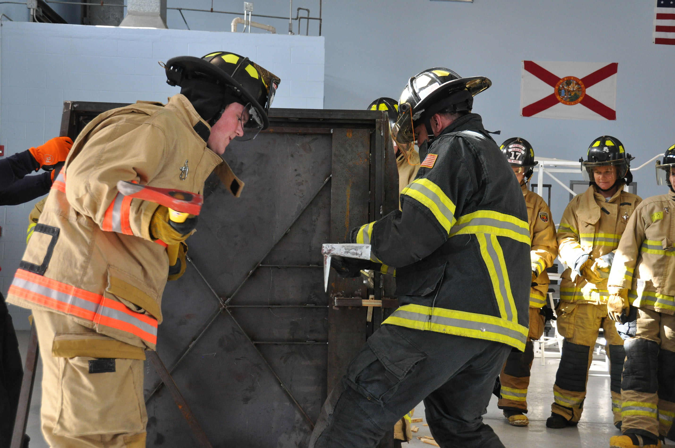 SFSC student Cole Choate wields an axe to breach a metal door in a  simulated forced