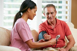 Home health aide work takes a patient's blood pressure reading.
